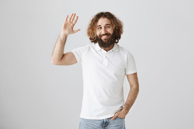 Homem simpático e simpático do oriente médio dizendo oi e acenando com a mão em um gesto de saudação