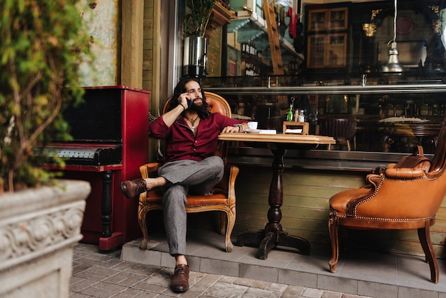 Homem simpático e simpático ligando enquanto descansava no café