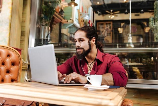Homem simpático e simpático sentado em frente ao laptop enquanto digita