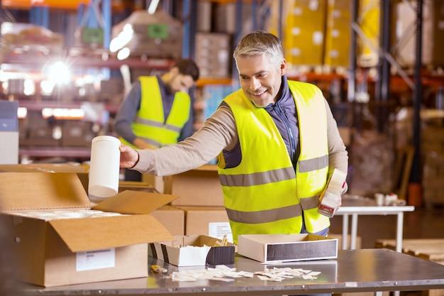 Homem simpático encantado colocando uma garrafa na caixa enquanto preparava o pacote