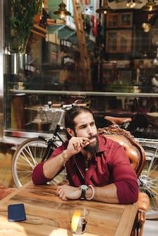 Homem simpático encantado, fumando um charuto enquanto está sentado do lado de fora no café