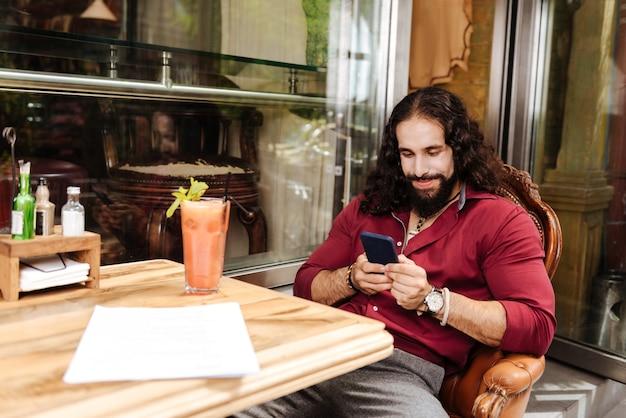 Homem simpático encantado usando seu smartphone enquanto está sentado no refeitório