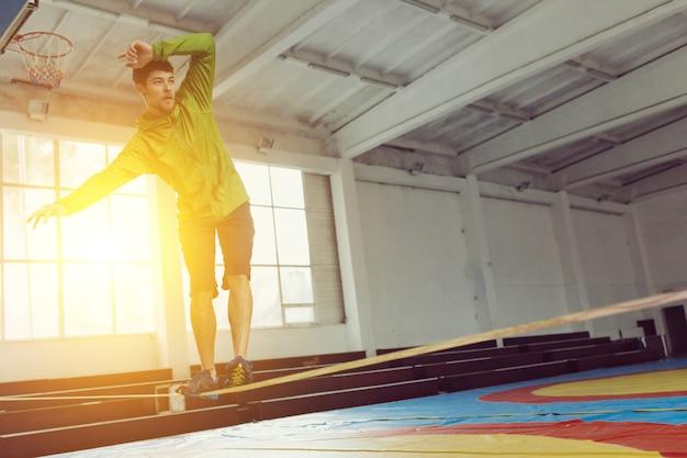 Homem slacklining andando e equilibrando em uma corda, slackline em um pavilhão desportivo