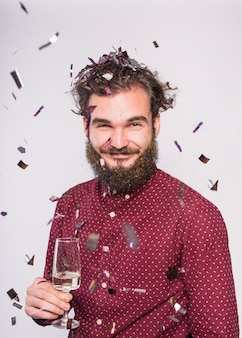 Homem sob lantejoulas com taça de champanhe