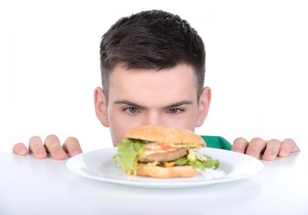 Homem sobe debaixo da mesa e olha para fast food.