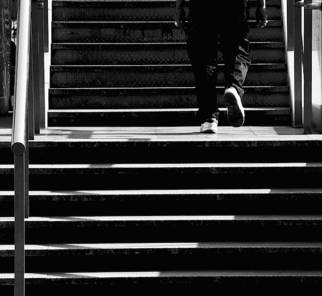 Homem sobe em uma escada de concreto na cidade - monocromático