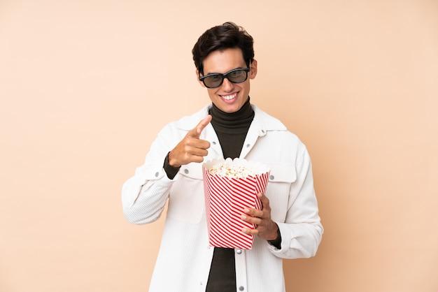 Homem sobre a parede com óculos 3d e segurando um grande balde de pipocas enquanto aponta a frente