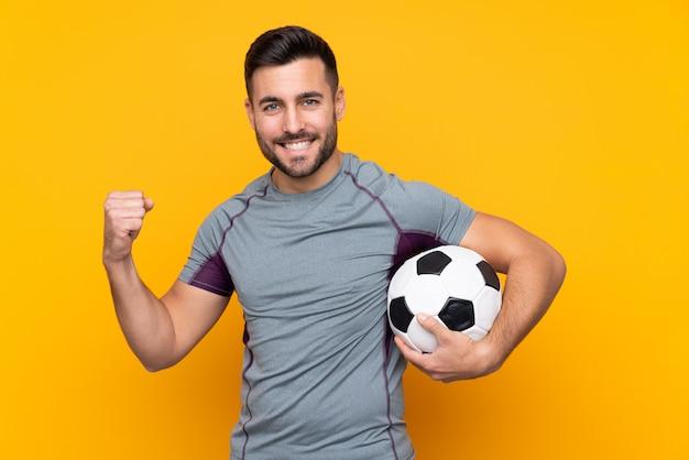 Homem sobre parede amarela isolada com bola de futebol comemorando uma vitória