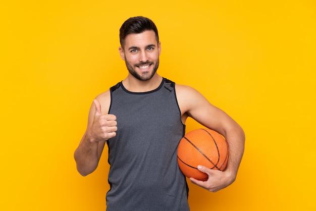 Homem sobre parede amarela isolada, jogando basquete e com o polegar para cima
