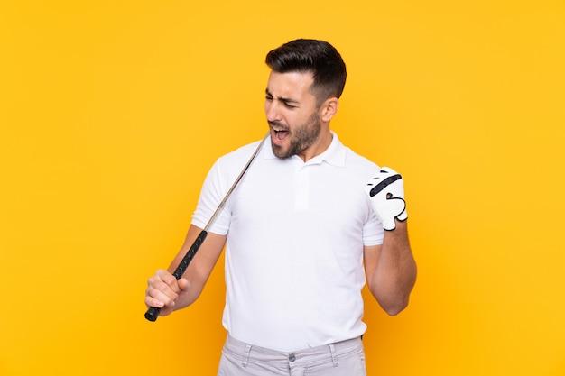 Homem sobre parede amarela isolada jogando golfe e comemorando uma vitória