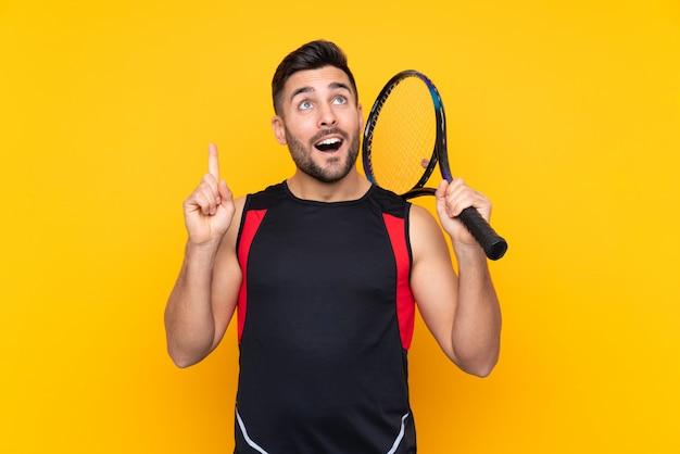 Homem sobre parede amarela isolada, jogando tênis e apontando para cima