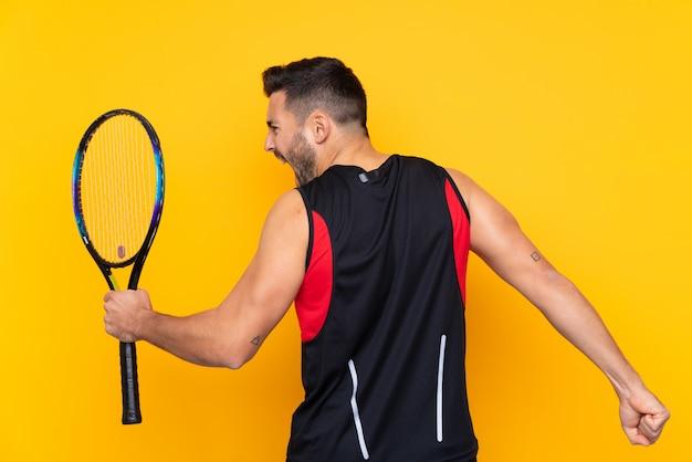 Homem sobre parede amarela isolada, jogando tênis e comemorando uma vitória