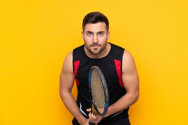 Homem sobre parede amarela isolada, jogando tênis