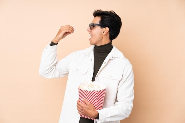 Homem sobre parede com óculos 3d e segurando um grande balde de pipocas