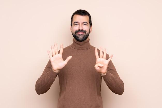 Homem sobre parede isolada, contando nove com os dedos