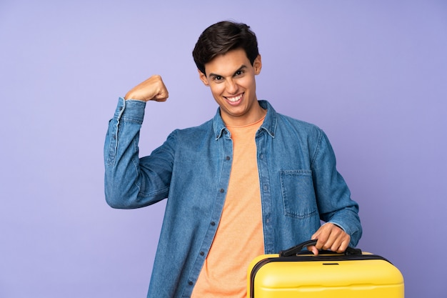 Homem sobre parede roxa em férias com mala de viagem e um chapéu