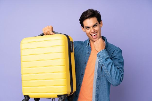 Homem sobre parede roxa em férias com mala de viagem
