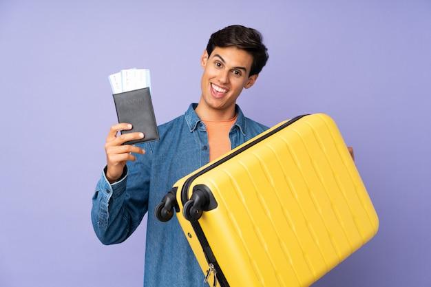 Homem sobre parede roxa em férias com mala e passaporte