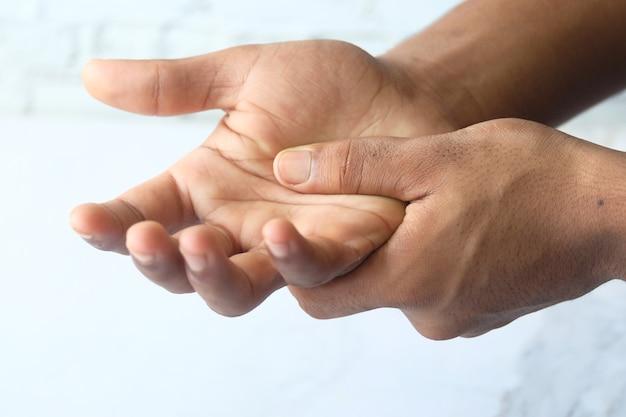 Homem sofrendo de dor na mão isolado no branco