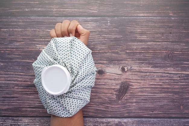 Homem sofrendo de dor nas mãos e colocando uma bolsa de água fria na mão Foto Premium