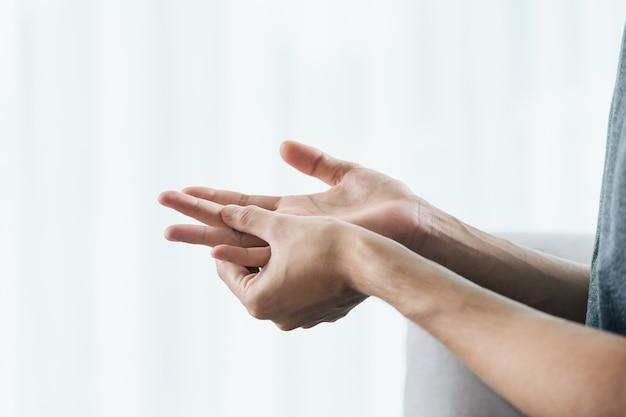 Homem sofrendo de dores nas mãos e nos dedos. causas da artrite reumatóide