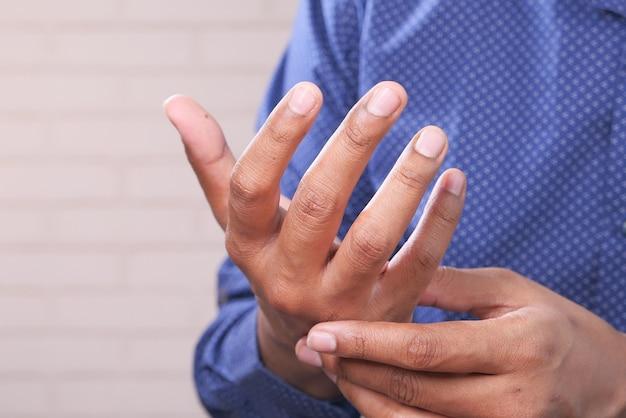 Homem sofrendo dor no dedo de perto