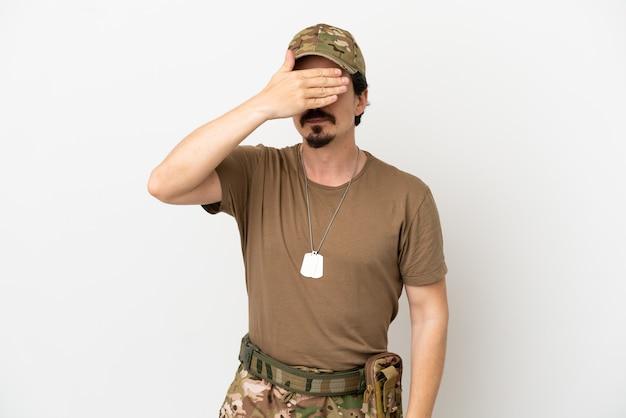 Homem soldado isolado no fundo branco, cobrindo os olhos pelas mãos. não quero ver nada