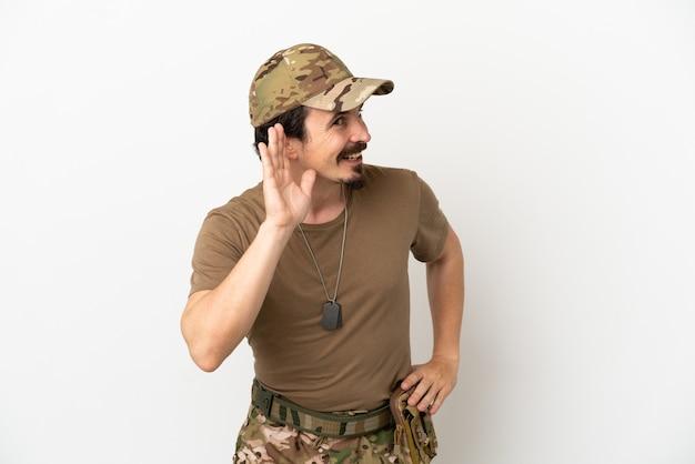 Homem soldado isolado no fundo branco ouvindo algo colocando a mão na orelha