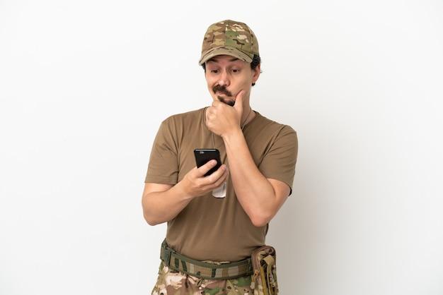 Homem soldado isolado no fundo branco pensando e enviando uma mensagem