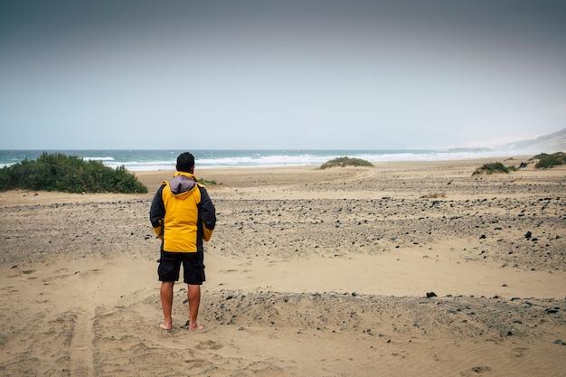 Homem solitário aventureiro caucasiano sozinho na praia em fuerteventura ninguém lá. praia natural ao ar livre com ondas fortes e mar. trekker de areia e pés descalços para uma viagem alternativa