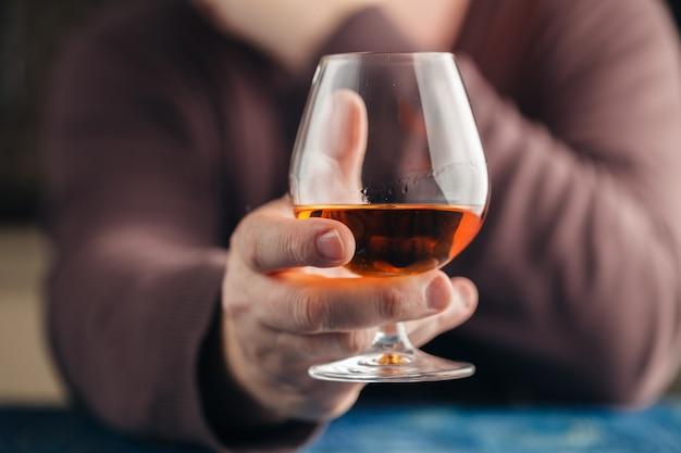 Homem solitário beber álcool na cozinha, abuso de alcoolismo