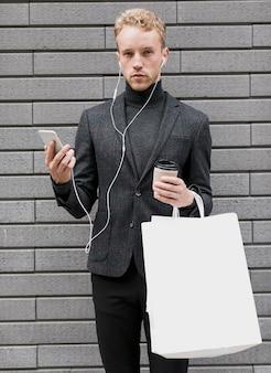 Homem solitário com sacos de compras e smartphone