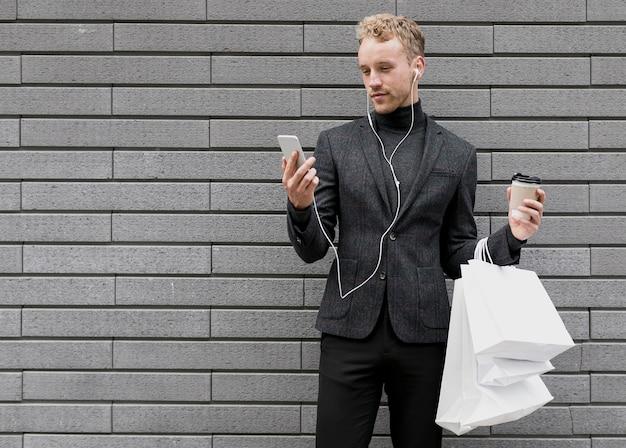 Homem solitário com sacos de compras, sorrindo para smartphone