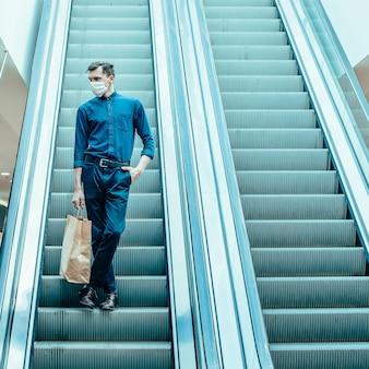 Homem solitário com uma máscara protetora em pé nos degraus da escada rolante.