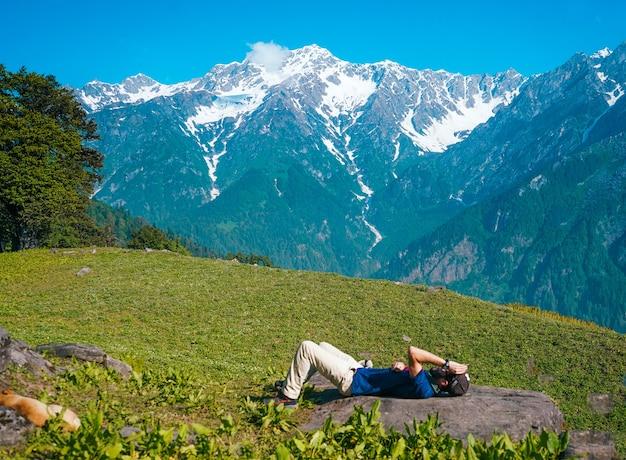 Homem solitário deitado e tomando banho de sol em uma campina com montanhas