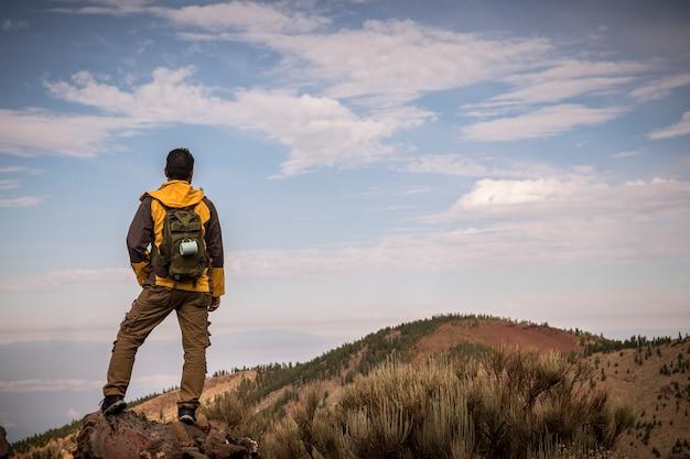 Homem solitário em aventura de trekking descobre atividade na montanha com mochila