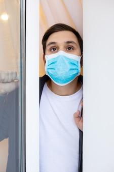 Homem solitário em quarentena com covid-19 em auto-isolamento em casa olha da janela. prevenção de pandemia de coronavírus. homem em quarentena de máscara médica protetora em casa.