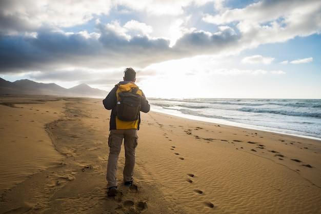 Homem solitário explorando a praia sem ninguém na costa selvagem
