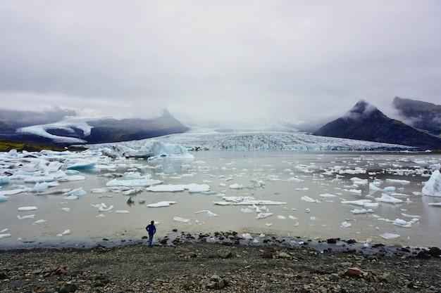 Homem solitário olha para o infinito na margem do glaciar fjallsarlon, islândia
