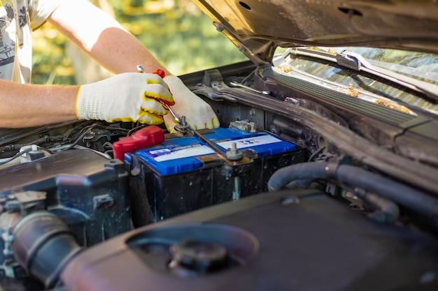 Homem solta os parafusos de montagem da bateria com uma chave inglesa, instalando e substituindo as peças sobressalentes em um carro.