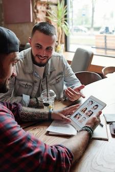 Homem solteiro sentado à mesa em um café pedindo conselhos a um amigo sobre o aplicativo de namoro enquanto visualiza perfis de mulheres no tablet