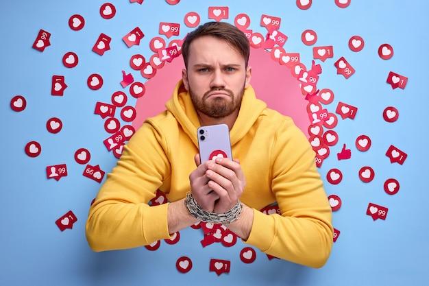Homem sombrio obcecado com internet. cara caucasiano bonito em roupas casuais, entre muitos gostos.