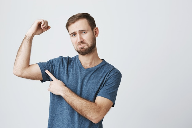 Homem sombrio reclamando, flexione os bíceps e franzindo a testa