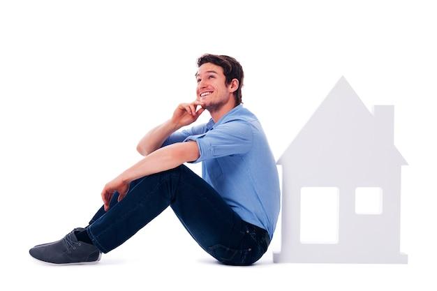 Homem sonhador sentado ao lado de uma placa para casa