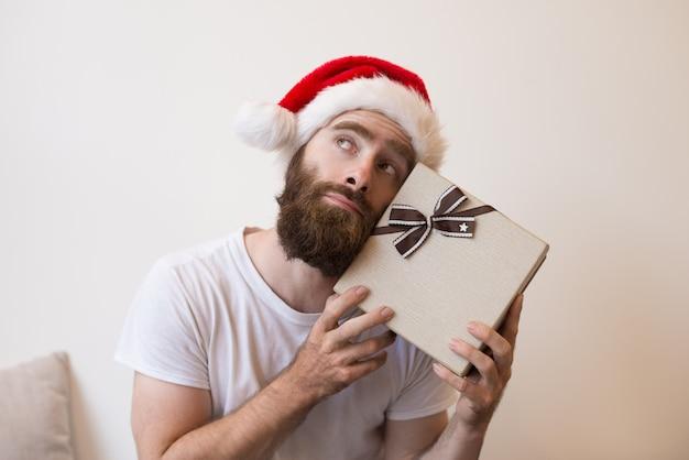 Homem sonhador tentando adivinhar o que está dentro da caixa de presente de natal