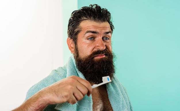 Homem sonolento com escova de dentes bocejo pasta de dente tratamentos matinais rotina de cuidados de saúde da manhã escovação
