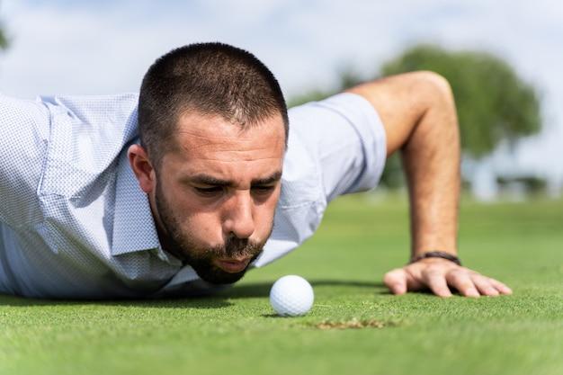 Homem soprando uma bola de golfe em um buraco