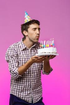 Homem soprando velas no bolo de aniversário sobre parede roxa.