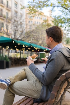 Homem sorridente a almoçar sentado no banco