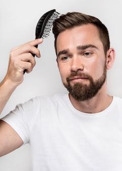 Homem sorridente a escovar o cabelo